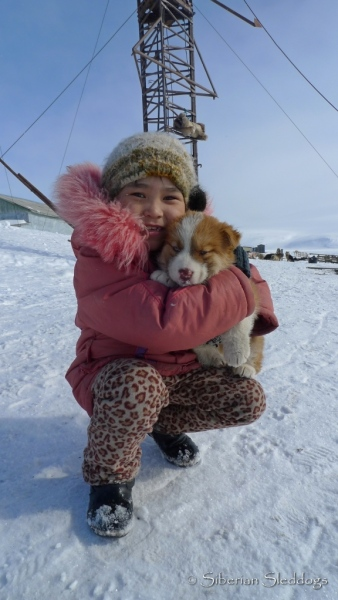 A young girl in Uelen holding a Chukchi puppy
